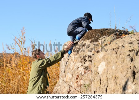 Scout helping a young boy rock climbing giving him a helping hand from below as he learns about the wilderness and nature - stock photo