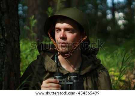 Scout in helmet with binoculars in summer forest