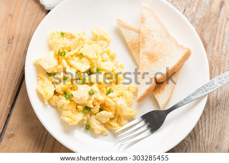 Scrambled egg and bread on white plate. Top view. - stock photo