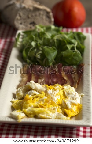 Scrambled eggs and fried bacon meal - stock photo