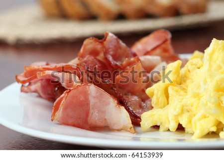 Scrambled eggs and slices of bacon on a plate - stock photo