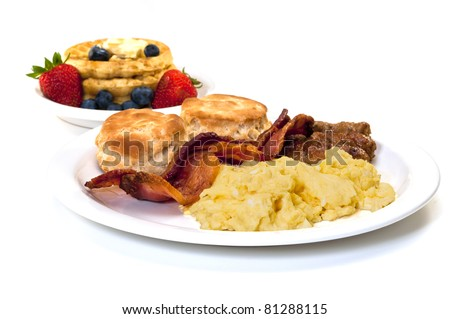 Scrambled eggs, bacon, link sausage, biscuits,  and waffles with strawberries and blueberries.  Isolated on white background. - stock photo