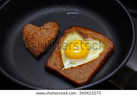 scrambled eggs, made in a piece of black bread. The bread is cut into a heart. Tasty breakfast for loved ones - stock photo