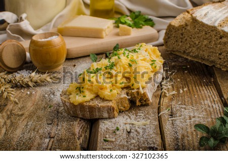 Scrambled eggs on homemade bread, beautiful rustic bread baked home in oven from homemade leaven - stock photo