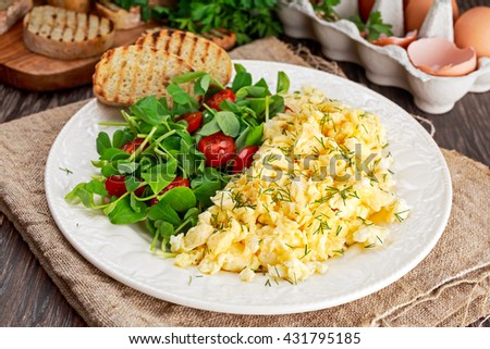 Scrambled eggs on plate with vegetables and grilled toast. - stock photo