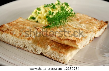 Scrambled eggs on turkish bread with shallots fennel and parsley.