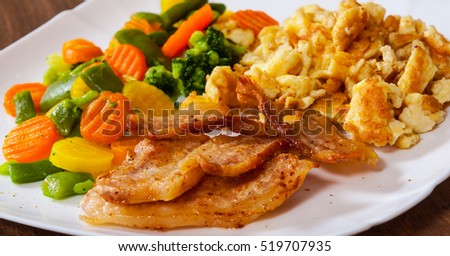scrambled eggs with bacon and vegetables mix in a plate on wooden table