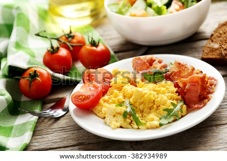 Scrambled eggs with bacon and vegetables on a grey wooden table - stock photo