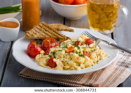 Scrambled eggs with baked tomatoes and chives, panini toast - stock photo
