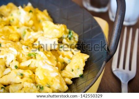 scrambled eggs with chives and herbs. Served in an iron pan. - stock photo