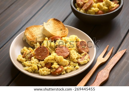 Scrambled eggs with chorizo slices and onion on plate with toasted baguette slices, wooden fork and knife on beside, photographed with natural light (Selective Focus, Focus one third onto the plate)  - stock photo