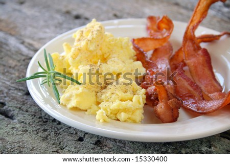 Scrambled eggs with crispy bacon on a plate, and garnished with a fresh sprig of Rosemary. - stock photo