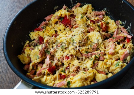 scrambled eggs with ham, vegetables and cheese in a frying pan on wooden table