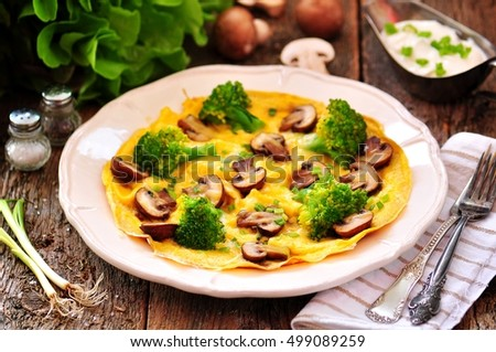 Scrambled eggs with mushrooms, broccoli, cheese and green onions on an ...