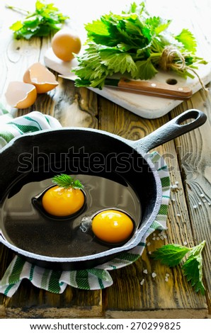 Scrambled eggs with nettles in a pan on a wooden table. Healthy food - stock photo