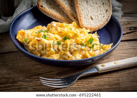 Scrambled Eggs With Onion And Chives Served With Bread On A Blue Plate