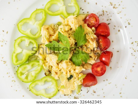 Scrambled eggs with paprika, cherry tomatoes and celery leaves. Rich breakfast. - stock photo