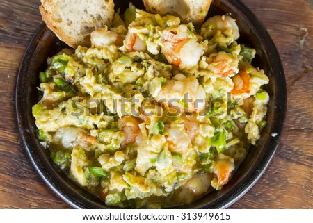Scrambled eggs with prawns and asparagus - stock photo