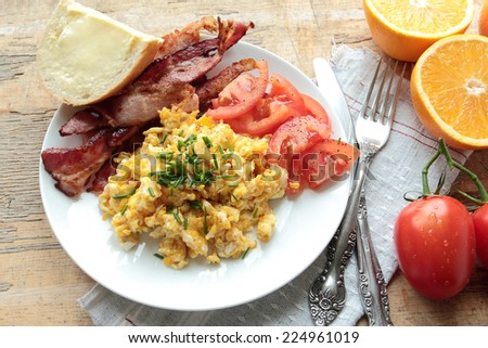 Scrambled eggs with tasty bacon and tomatoes - stock photo