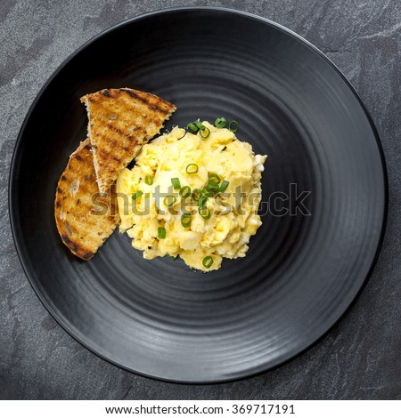 Scrambled eggs with toast on black plate. Overhead view. - stock photo