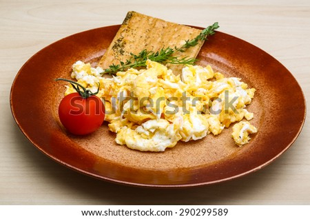 Scrambled eggs with tomato, dill and black olive