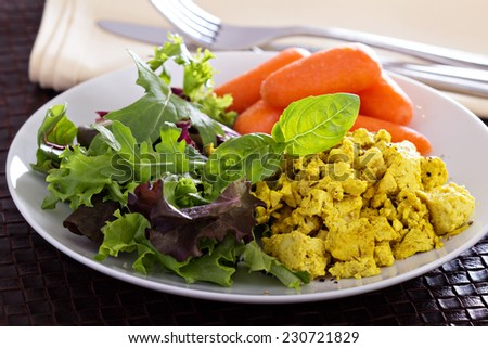 Scrambled tofu with salad leaves and carrot for breakfast - stock photo
