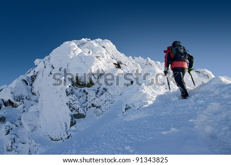 Scrambler with ice axe is going up in mountains. WinterPolish High Tatra Mountains. - stock photo