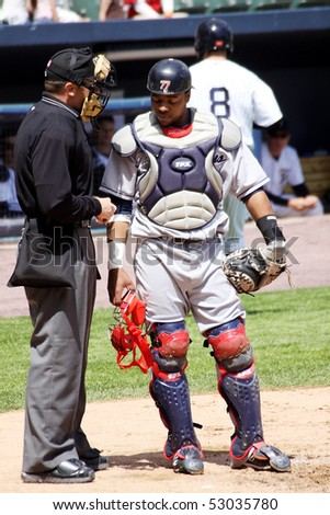 SCRANTON - May 13: The Columbus Clippers catcher Carlos Santana talks with an umpire in a game against Scranton Wilkes Barre Yankees in a game at PNC Field May 13, 2010 in Scranton, PA - stock photo