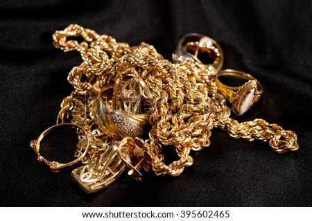 scrap gold jewelery including chains, bracelets and rings on a black background