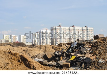 Scrap heap near the new buildings in a city new district.  - stock photo
