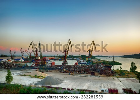 Scrap metal base with cranes on the river - stock photo