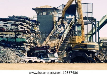 Scrap metal junk yard, giant crane picking up pieces of old cars for recycling. - stock photo