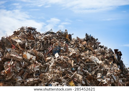 Scrap metal ready for recycling over blue sky. - stock photo