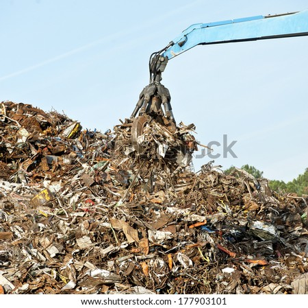 Scrap metal recycling plant and crane-Loading scrap in a truck - stock photo