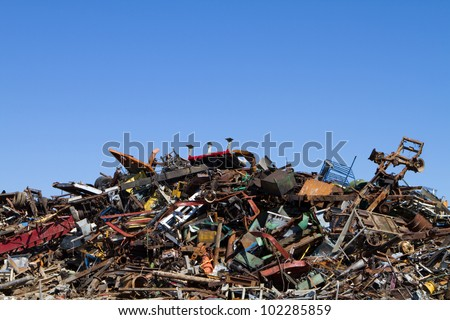 Scrap metal waste is stored in a recycling yard waiting to be melted down to manufacture new products. - stock photo