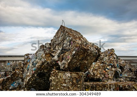 Scrap Steel ready for recycling over dark clouds. - stock photo