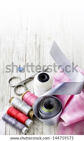 Scrapbooking craft materials/Background with sewing tools and colored tape/Sewing kit. Scissors, bobbins with thread and needles on the old wooden background - stock photo