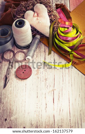 Scrapbooking craft materials/ Background with sewing tools and colored tape/Sewing kit. Scissors, bobbins with thread and needles on the old wooden background - stock photo
