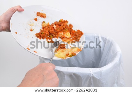 Scraping food waste from a plate into a garbage bin - stock photo