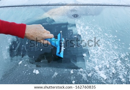 Scraping ice from the car window  - stock photo