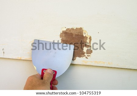 scraping old paint from siding with a putty knife in preparation for painting - stock photo