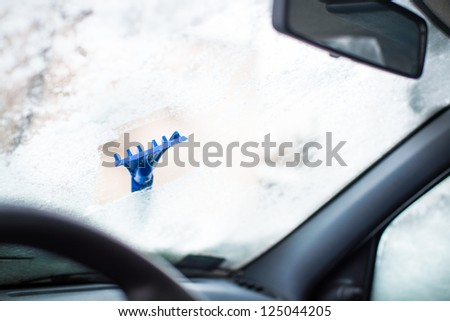 Scrapping frozen car window with blue ice scrapper - stock photo