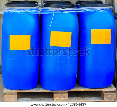 Scratched blue barrels packed with orange labels on wooden pallets
