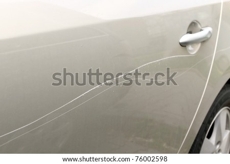 Scratched car paint with door handle and tire out of focus - stock photo