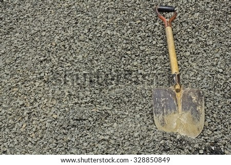 scratched shovel on rocks in a building site. - stock photo