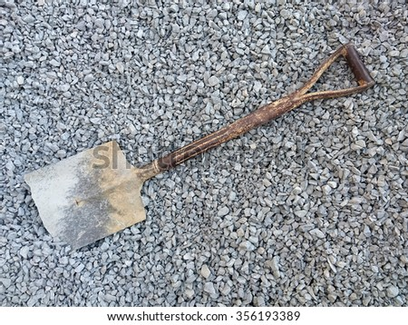 scratched shovel on rocks in a building site
