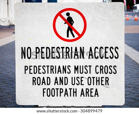 Scratched temporary traffic sign and symbol NO PEDESTRIAN ACCESS, PEDESTRIANS MUST CROSS ROAD AND USE OTHER FOOTPATH - stock photo