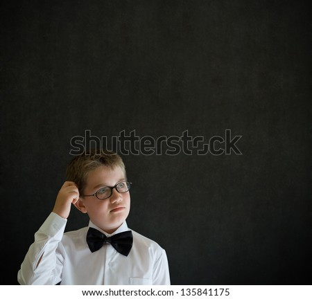 Scratching head thinking boy dressed up as business man, teacher or student on blackboard background - stock photo