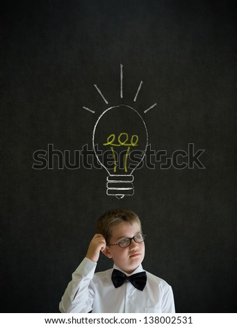 Scratching head thinking boy dressed up as business man with bright idea chalk background lightbulb on blackboard background