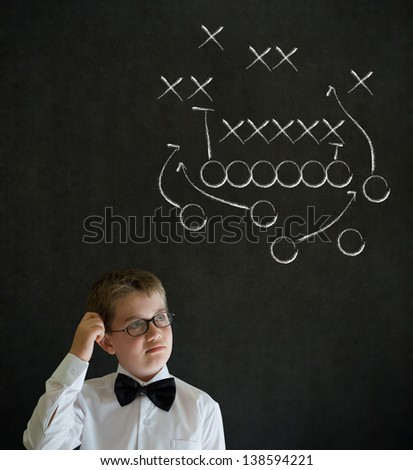 Scratching head thinking boy dressed up as business man with chalk American football strategy on blackboard background